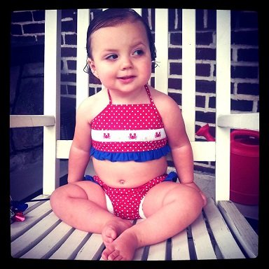 Stephanie from MD: This is my 14-month-old daughter, Piper, modeling her red, white and blue crab swimsuit on the Fourth of July! Love her expression here!